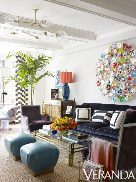 Furnishings with strong shapes and deep colors ground vivacious art in the living room. Custom sofa in a JB Martin fabric; armchairs in a Holland & Sherry fabric, Todd Alexander Romano; vintage Karl Springer ottomans in a Moore & Giles leather; coffee table, John Salibello; chandelier, Lindsey Adelman; rug, Merida; art, Klari Reis.