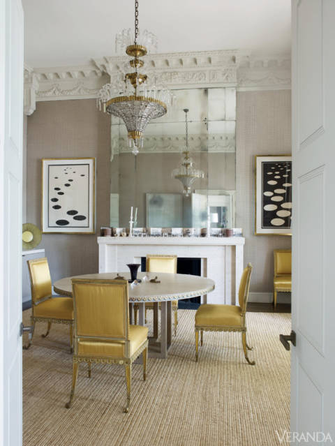 For the living and dining rooms, Grenney designed stunning travertine fireplace surrounds that allude to the period. Above them, his tall, antiqued mirrored panels also nod to the past, as do the soaring fifteen-foot ceilings. Chairs, Cove Landing, in Claremont silk. Jansen chandelier. Mantel and linen on walls, both custom. Art, Alexander Calder.